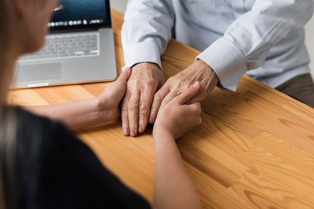 Verpleegster die de handen van de hogere man voor opluchting houdt