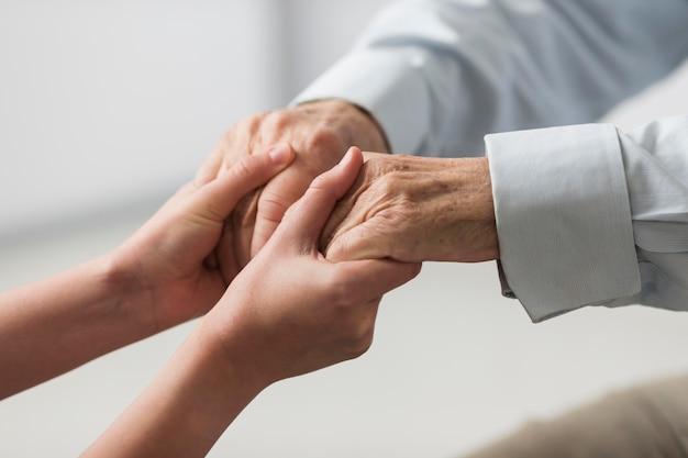 Verpleegster die de handen van de hogere man voor sympathie houdt