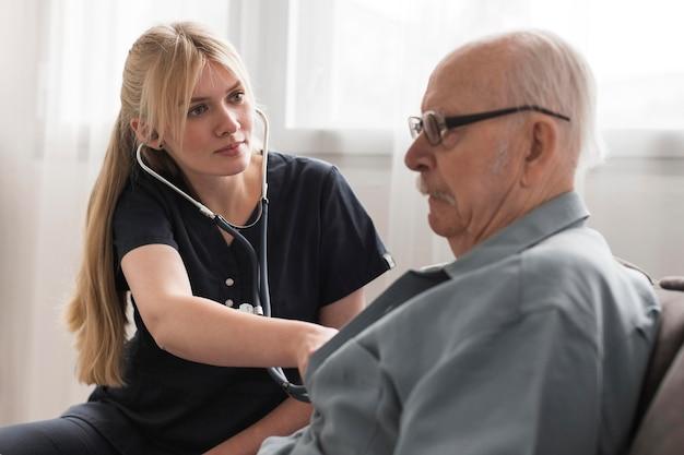 Verpleegster die de hartslag van de oude man controleert