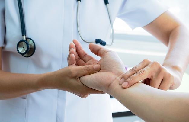 Verpleegster die de impuls van de patiënt controleren, het medische controleren impuls door hand. medisch en gezondheidszorgconcept.