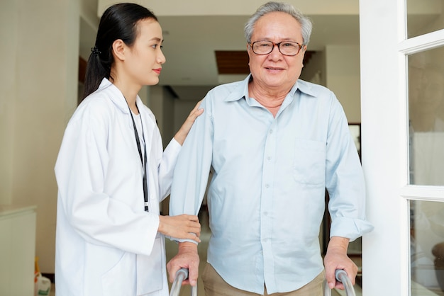 Verpleegster die de jonge mens helpt zich te bewegen