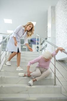 Verpleegster die de oudere vrouw hielp die op de zijgaren viel