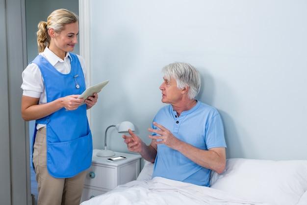 Verpleegster die digitale tablet houdt bij het ziekenhuis