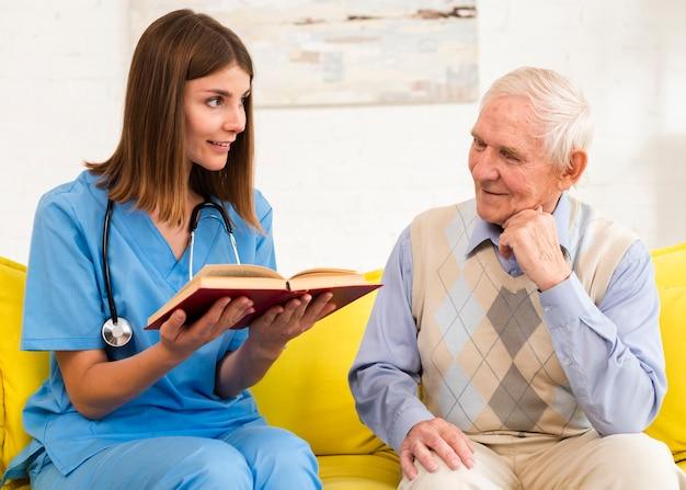 Verpleegster die een boek leest aan een oude man