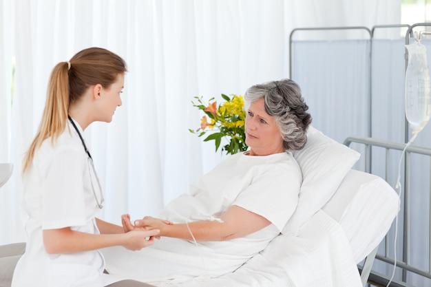 Verpleegster die een druppel op de arm van haar patiënt legt
