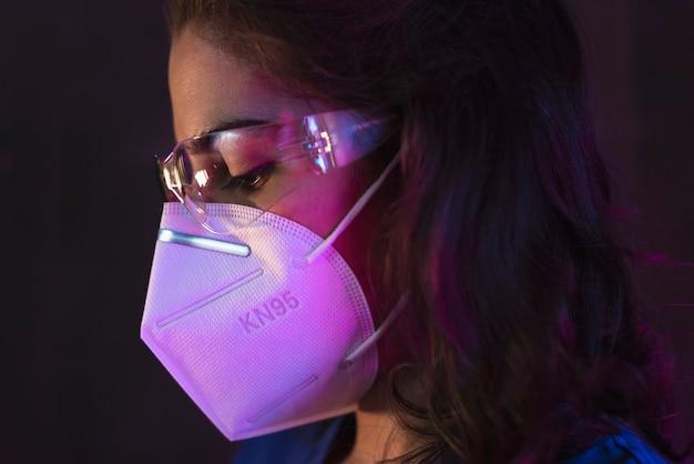 Verpleegster die een hazmatpak, een veiligheidsbril en een antiviraal masker kn95 draagt voor covid19