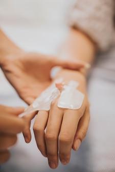 Verpleegster die een iv infuus met een patiënt toepast