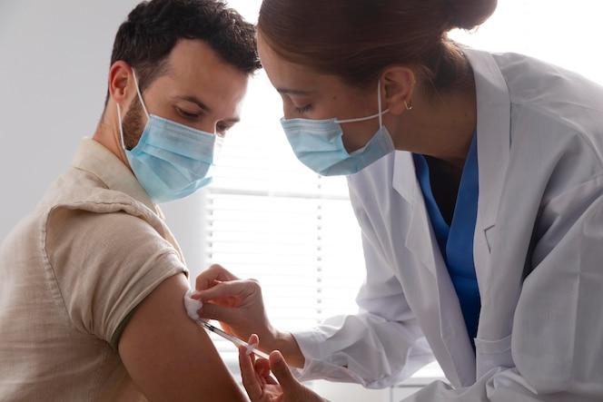 Verpleegster die een mannelijke patiënt vaccineert