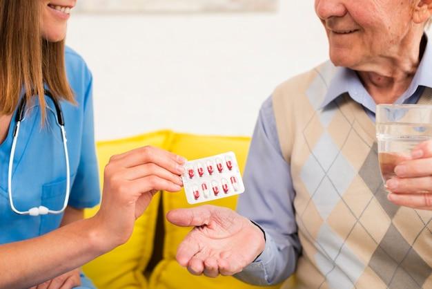 Verpleegster die een oude man zijn pillenclose-up geeft