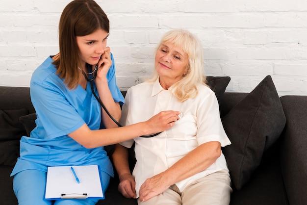Verpleegster die een oude vrouw met haar stethoscoop controleert
