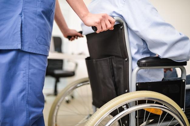 Verpleegster die een patiënt op een rolstoel behandelt