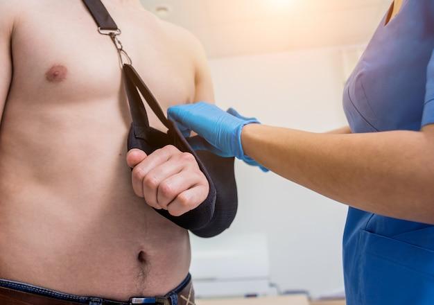 Verpleegster die een slinger op gebroken patiëntenwapen zet. letsel