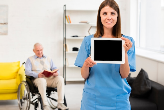 Verpleegster die een tabletmodel houdt
