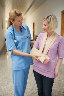 Verpleegster die gebroken arm van patiënt raakt
