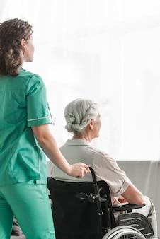 Verpleegster die gehandicapte patiënt op wielstoel in het ziekenhuis duwen