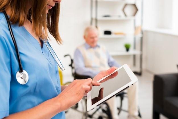 Verpleegster die haar tabletclose-up controleert
