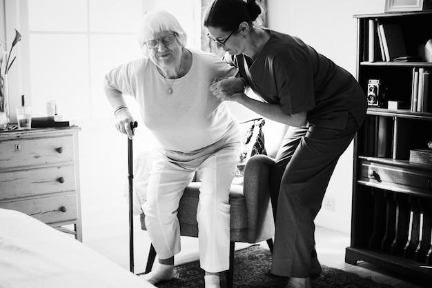Verpleegster die hogere vrouw helpen om zich te bevinden