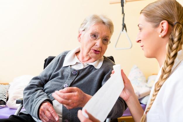 Verpleegster die hogere vrouw in pensioneringshuis behandelt