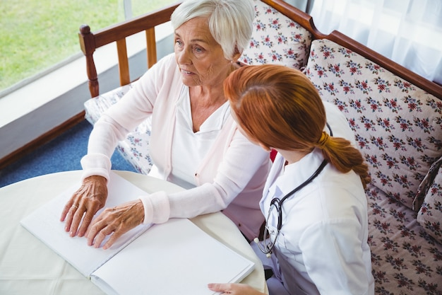 Verpleegster die hogere vrouw met braille helpt