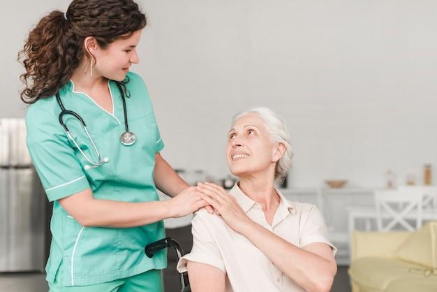 Verpleegster die hulp geeft aan gehandicapte vrouwelijke hogere geduldige zitting op rolstoel