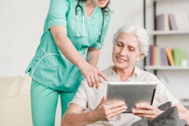Verpleegster die iets toont aan hogere vrouwelijke patiënt op digitale tablet