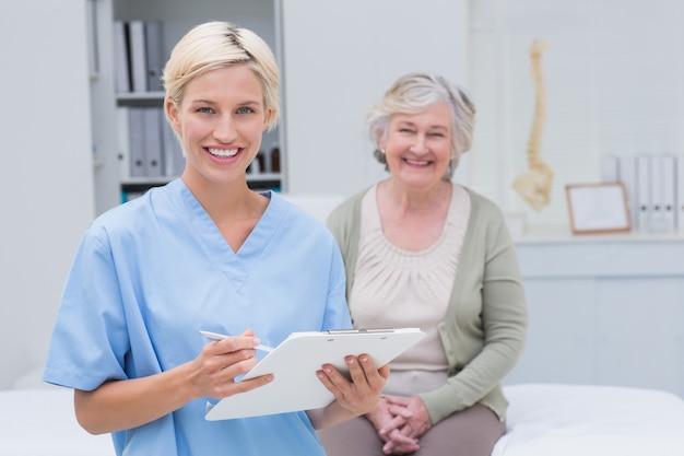 Verpleegster die klembord houden terwijl vrouwelijke geduldige zitting in kliniek