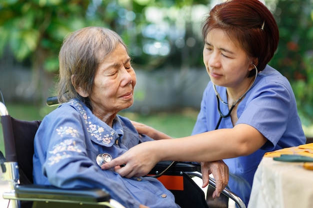 Verpleegster die longen van bejaarde vrouw controleert tijdens medische thuiszorg