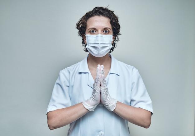Verpleegster die masker en handschoenen draagt die met gesloten handpalmen bidden