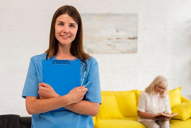 Verpleegster die met blauw klembord de camera bekijkt