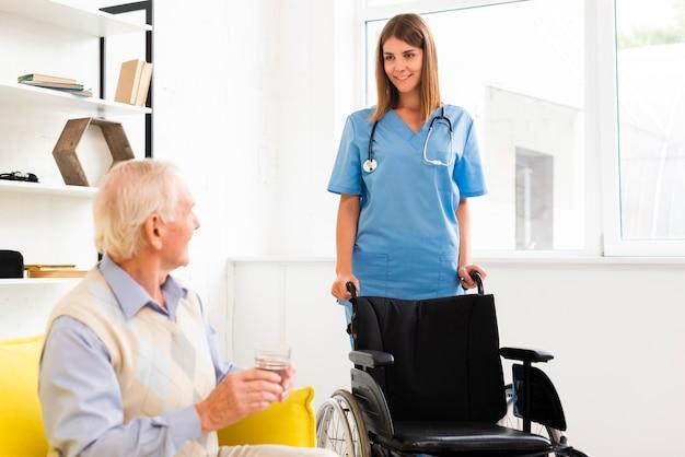 Verpleegster die met een rolstoel komt