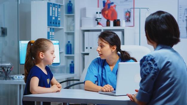 Verpleegster die met kind spreekt en meisjessymptomen op laptop schrijft. arts arts specialist in geneeskunde die gezondheidszorgdiensten overleg diagnostisch onderzoek behandeling in ziekenhuiskabinet biedt