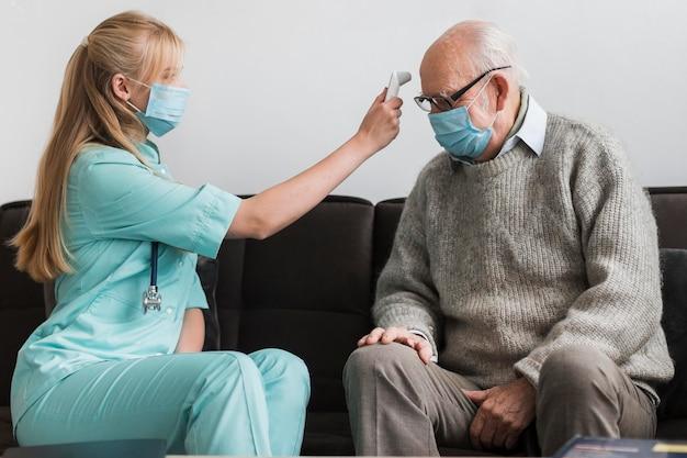 Verpleegster die met medisch masker de temperatuur van de oude man controleert