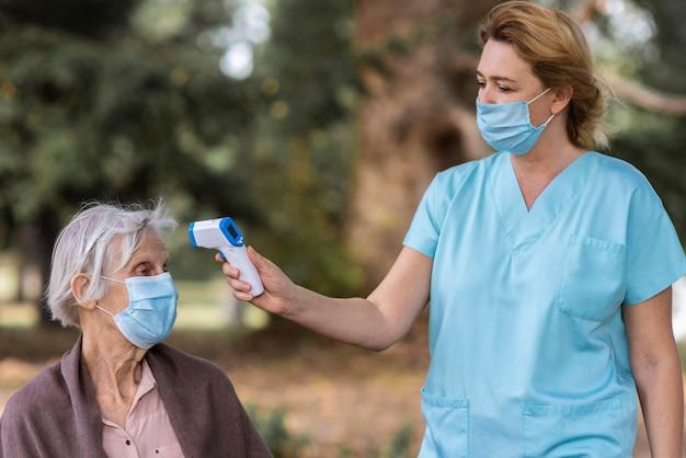 Verpleegster die met medisch masker de temperatuur van de oudere vrouw controleert