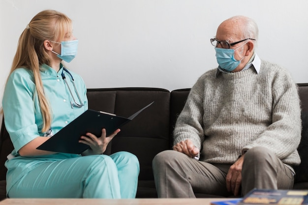 Verpleegster die met medisch masker oude man in een verpleeghuis onderzoekt