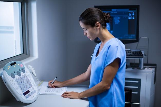 Verpleegster die nota's in x-ray ruimte maakt