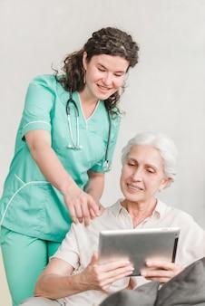 Verpleegster die op het scherm richten die iets tonen aan haar patiënt op digitale tablet