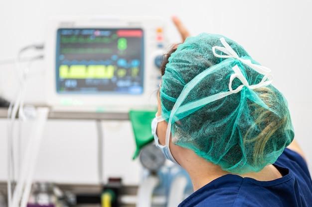Verpleegster die op intensive careafdeling werkt. mechanisch ventilatiesysteem
