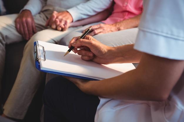 Verpleegster die op klembord schrijft