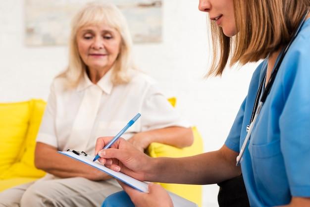 Verpleegster die op klembordclose-up schrijft