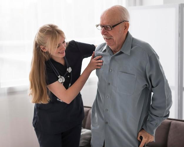 Verpleegster die oude man helpt opstaan