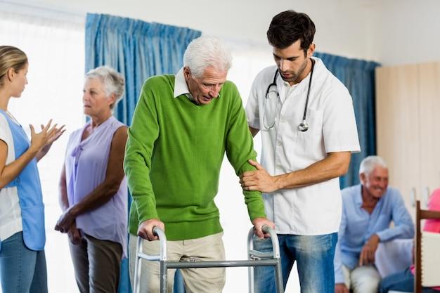 Verpleegster die oudste helpt met loophulp