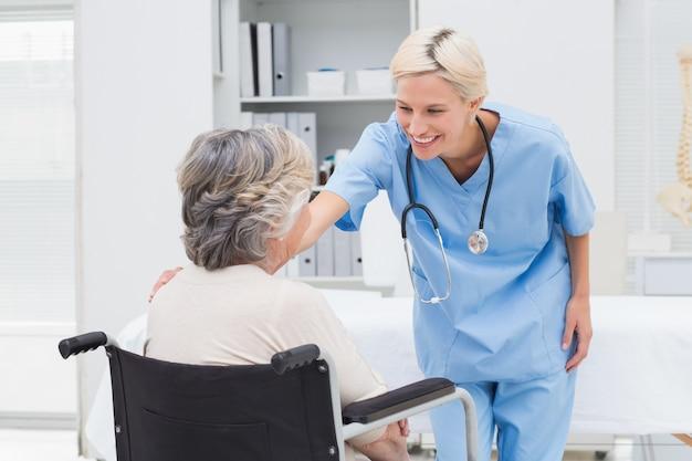 Verpleegster die patiënt troosten die op rolstoel zit