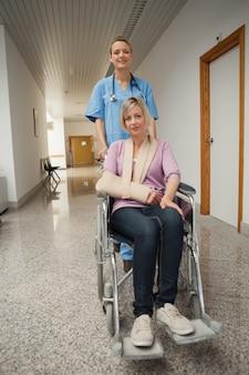 Verpleegster die rolstoel van patiënt met wapening duwen