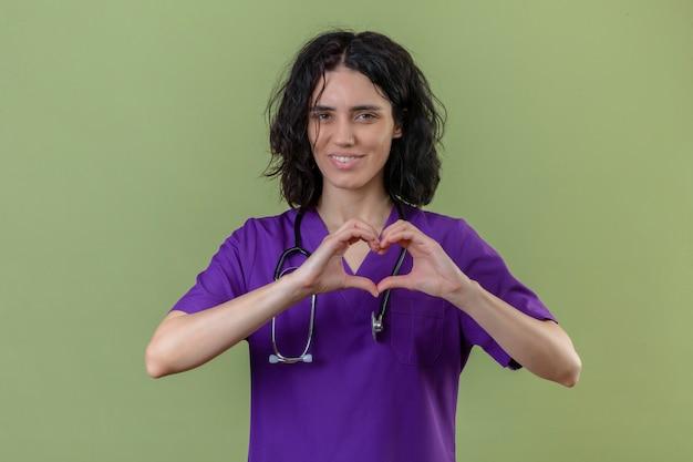 Verpleegster die uniform en stethoscoop draagt die romantisch hartgebaar op borst met glimlach op gezicht maakt die zich op geïsoleerde groen bevinden