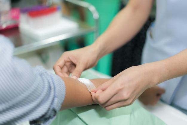 Verpleegster die verband op de hand van de patiënt na bloedonderzoek in het ziekenhuis toepast.