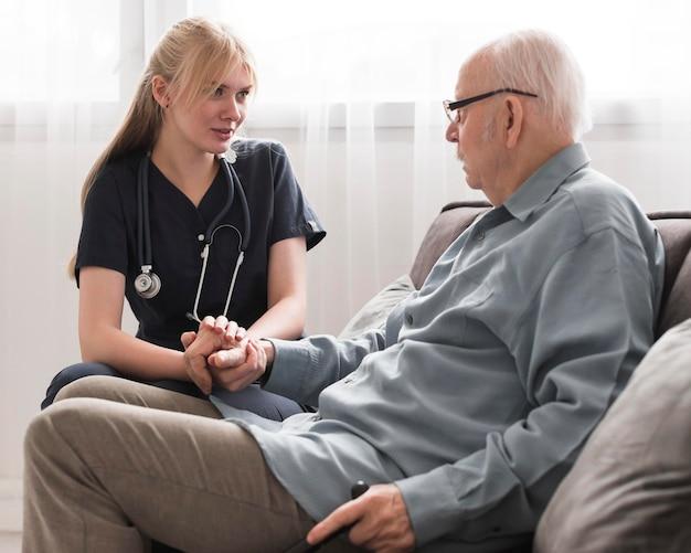 Verpleegster die voor de oude man zorgt