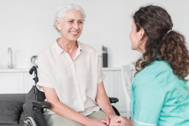 Verpleegster die vrouwelijke hogere patiënt op wielstoel bekijkt