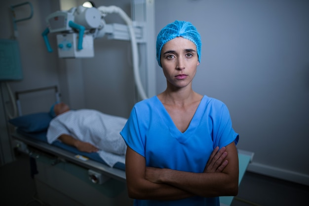 Verpleegster die zich met wapens bevinden die in x-ray ruimte worden gekruist
