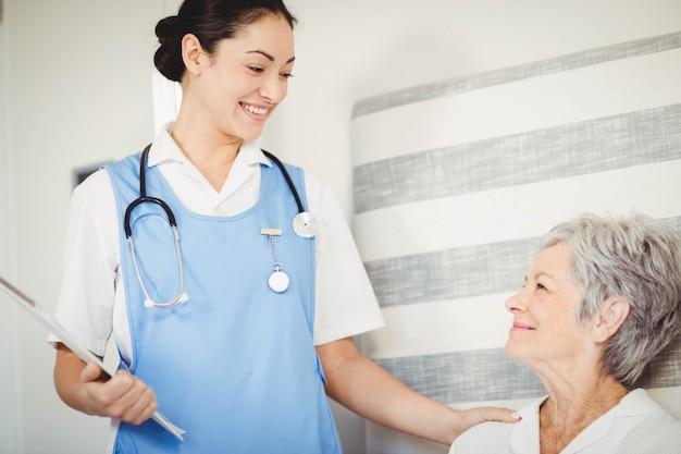 Verpleegster die zieke hogere vrouw in slaapkamer behandelt
