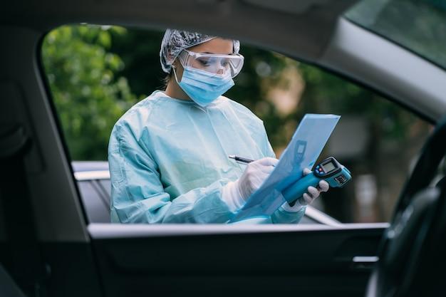 Verpleegster draagt een beschermend pak en masker tijdens de covid19-uitbraak.